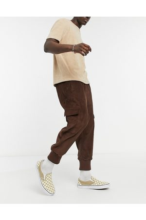 ASOS Oversized drop crotch trousers with cargo pockets & jersey cuffs in cord-Brown
