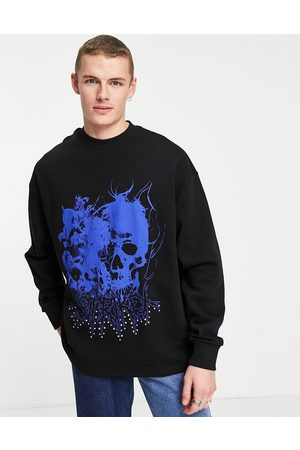 ASOS Oversized sweatshirt in black with gothic skull print and metal stud details